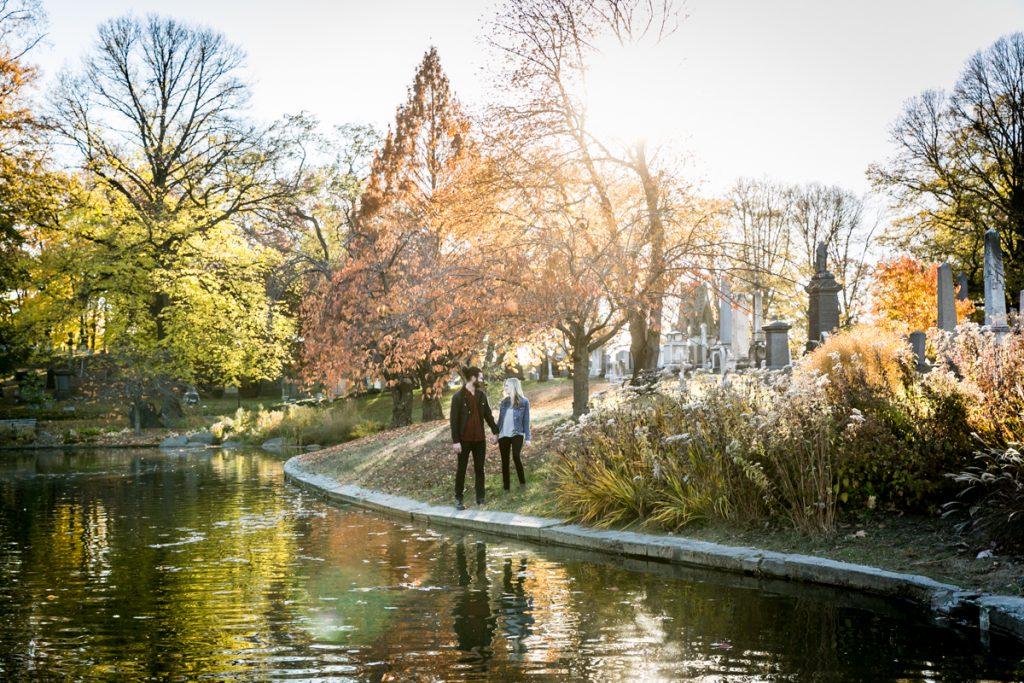 Green-Wood Cemetery engagement photos of couple walking along pond