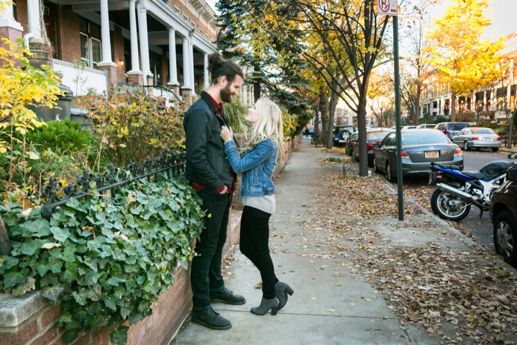 Windsor Terrace engagement photos of woman holding man by jacket on sidewalk