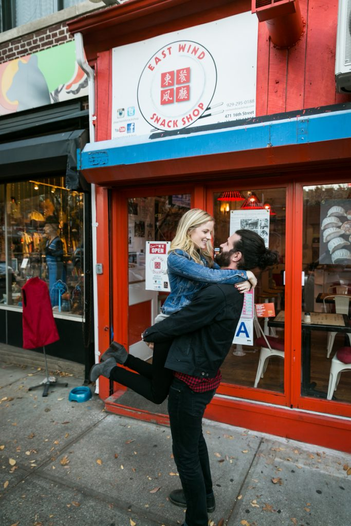 Windsor Terrace engagement photos of man lifting up woman in front of Chinese restaurant