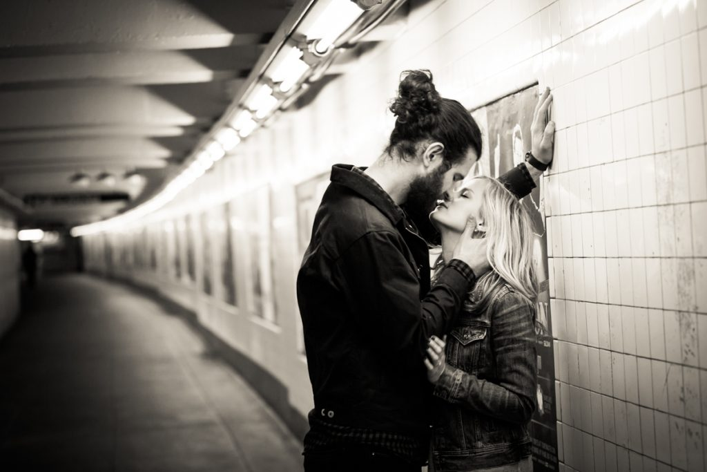 Black and white photo of couple kissing in subway station