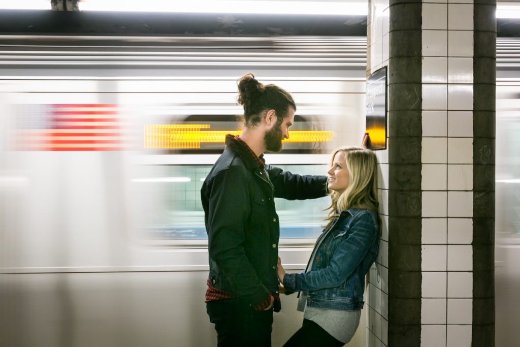 Couple leaning against column as subway car speeds past