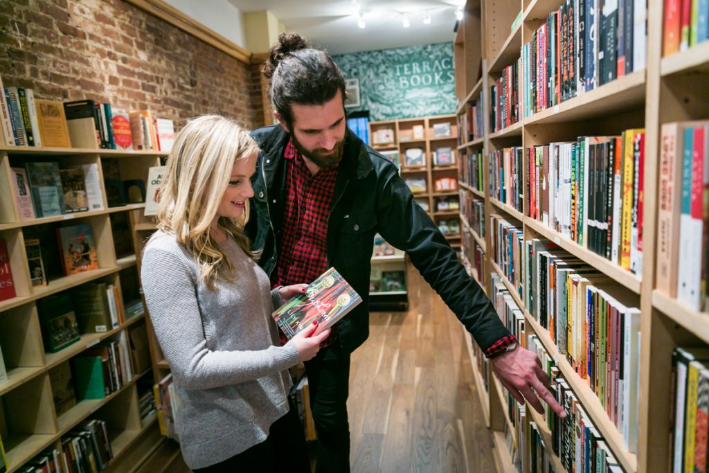 Couple in bookstore looking at books