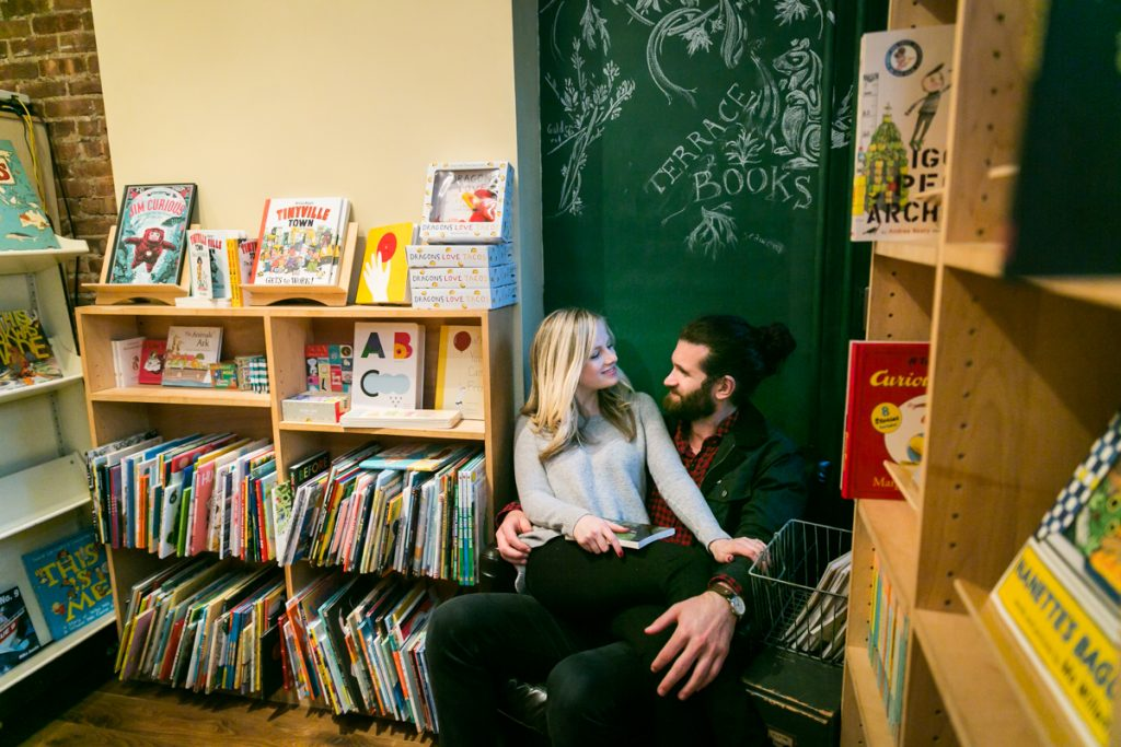 Woman sitting on man's lap in bookstore