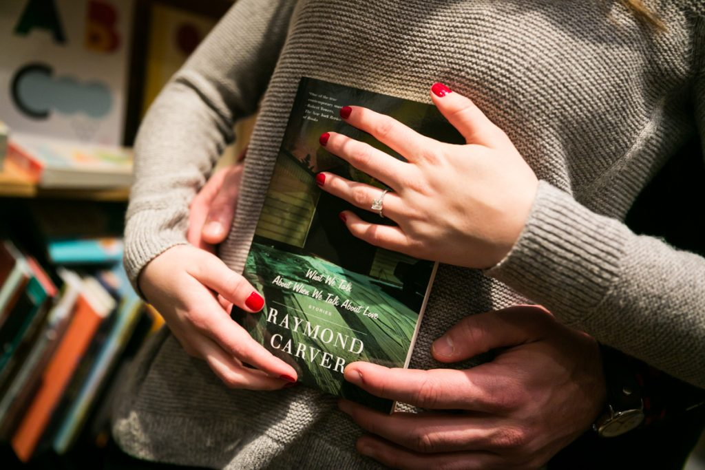 Close up of couple's hands holding books