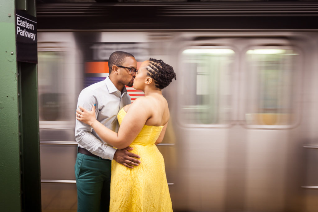 Couple kissing with speeding subway train for an article on best engagement photos