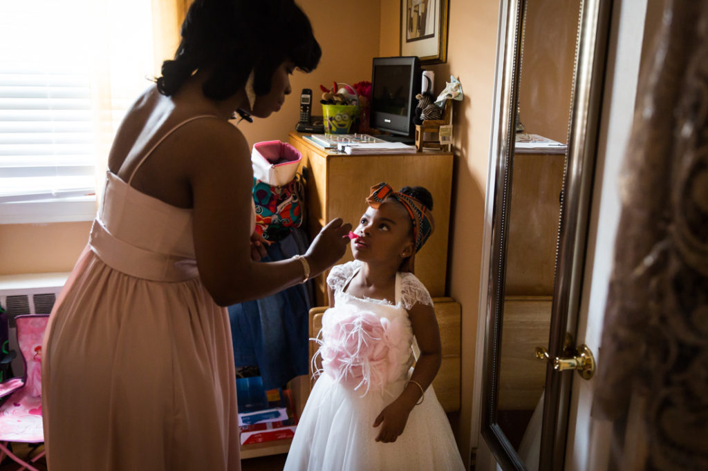 Little girl getting lipstick before a Glen Terrace wedding