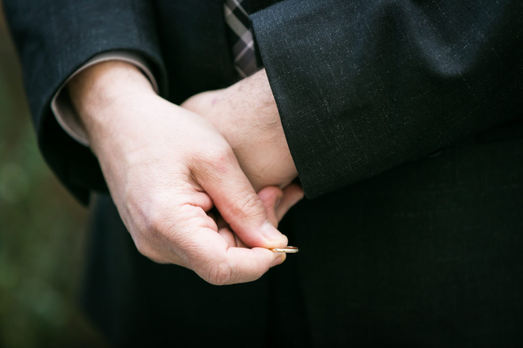 Hands holding a wedding ring for an article on the top fears about wedding photographers
