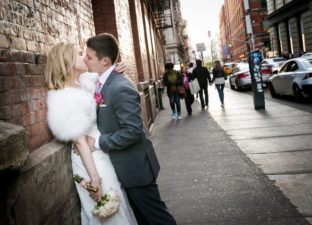 Couple kissing against wall in SoHo