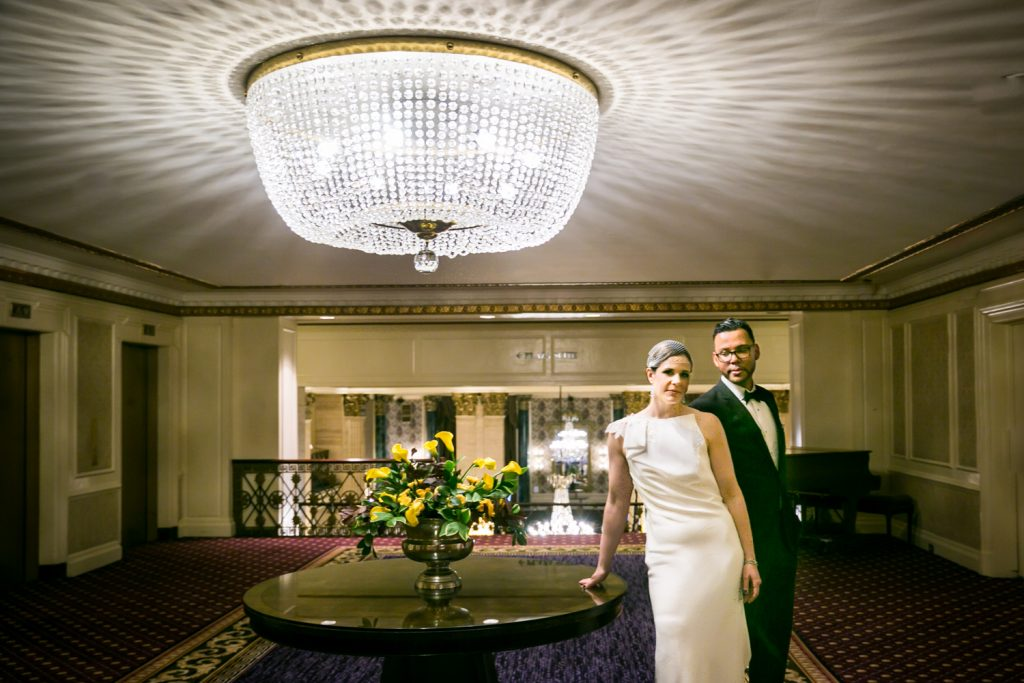 Couple standing under chandelier in Roosevelt Hotel for a NYC wedding destination guide