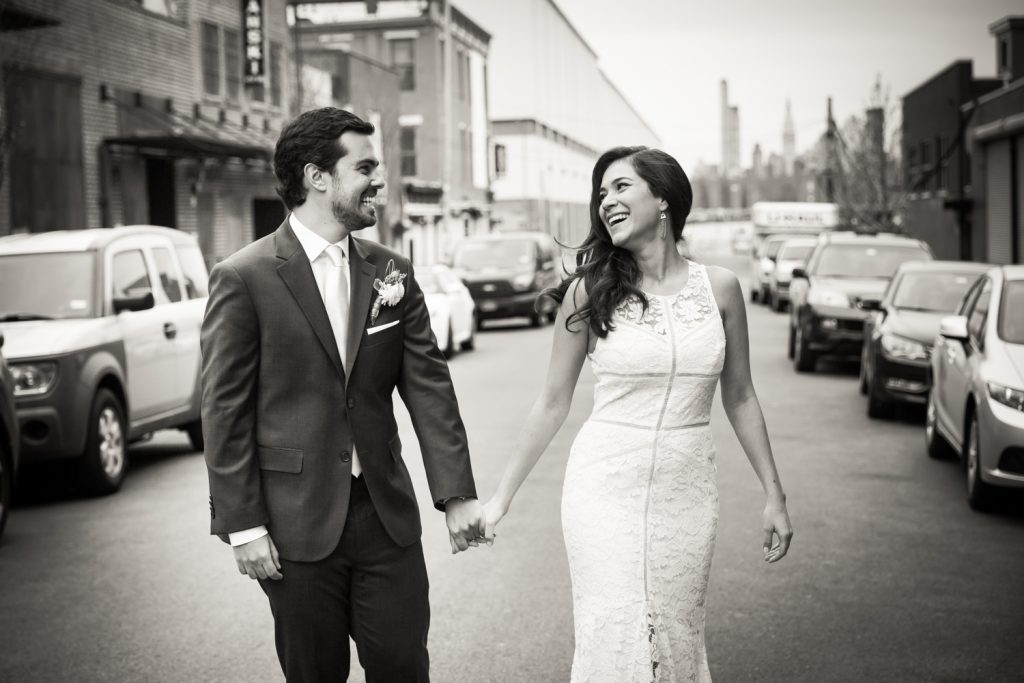Black and white photo of bride and groom walking hand in hand on Brooklyn street