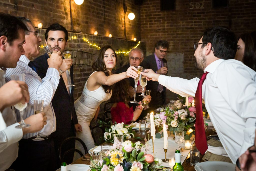 Bride toasting champagne glass with guest across table