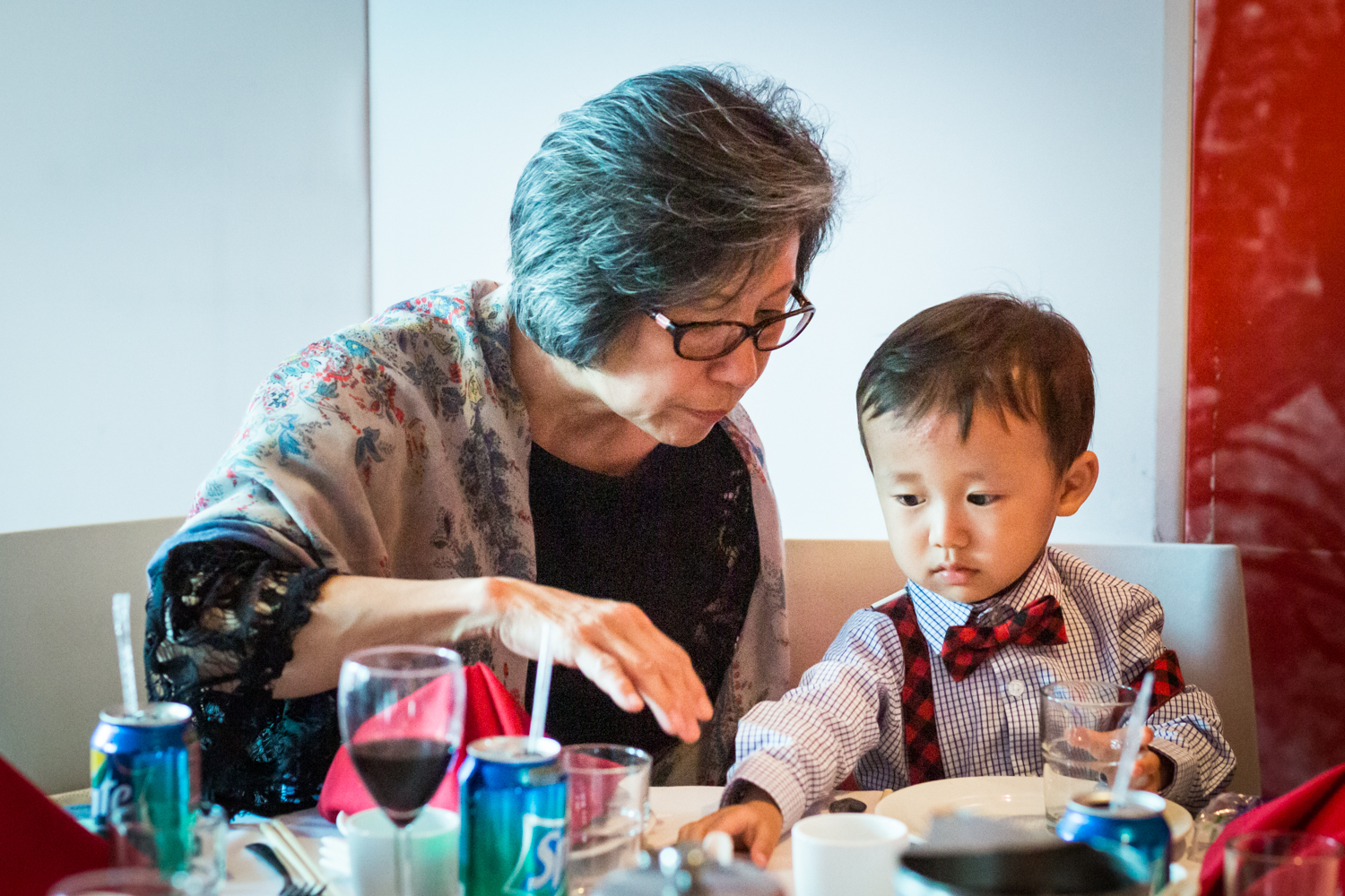 Grandmother helping little boy at a Chinatown rehearsal dinner