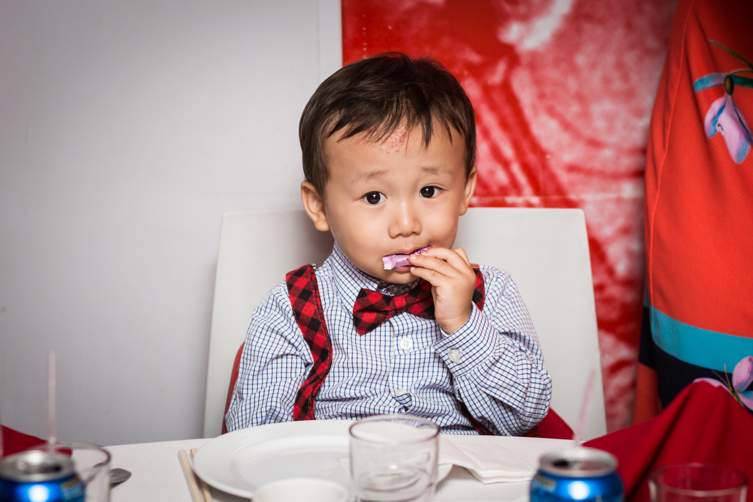 Little boy wearing bow tie and eating at a Chinatown rehearsal dinner
