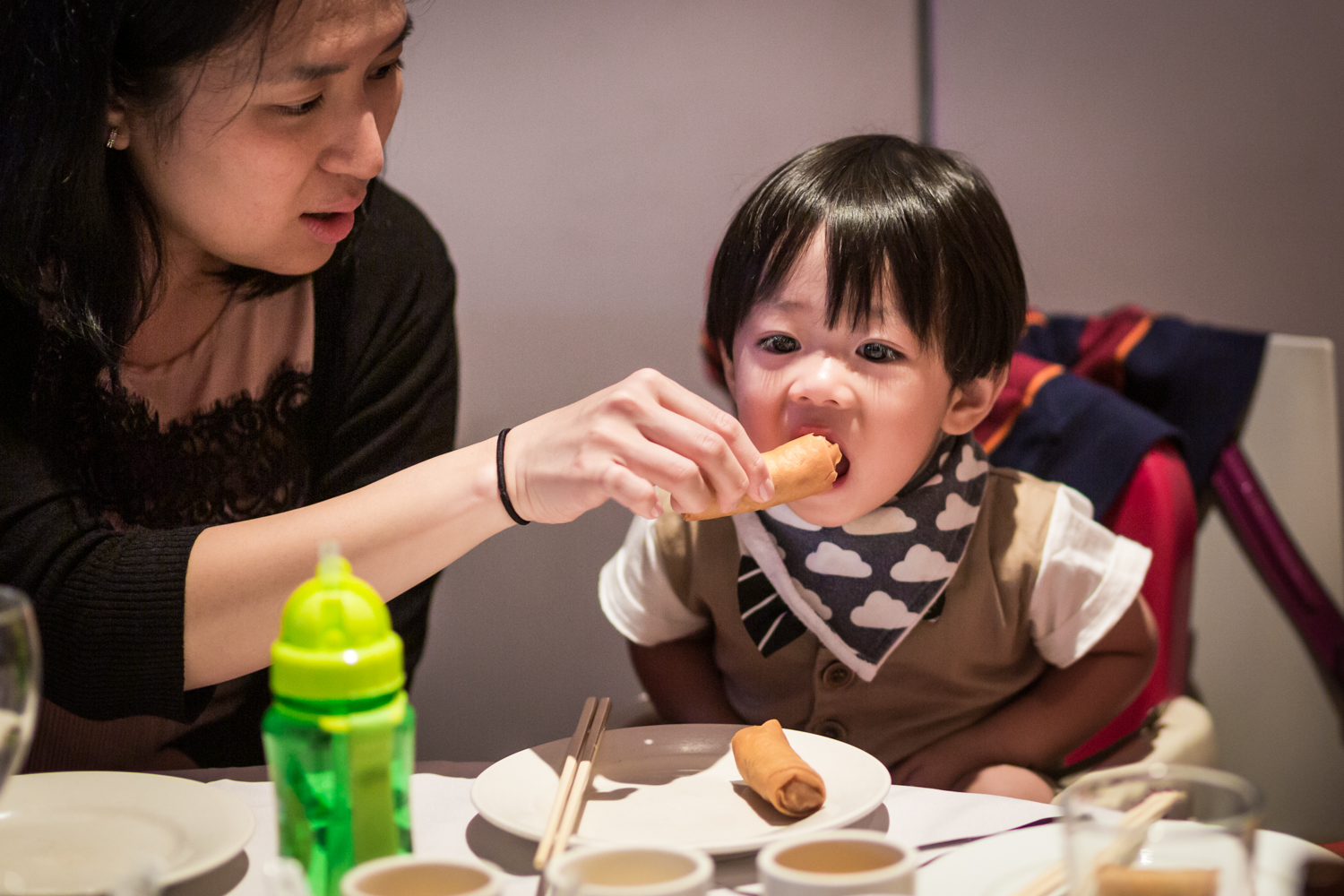 Mother feeding egg roll to little boy at a Chinatown rehearsal dinner