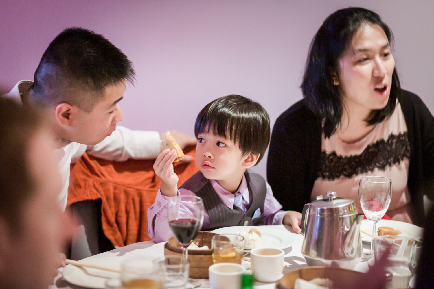 Little boy trying to give food to his father at a Chinatown rehearsal dinner