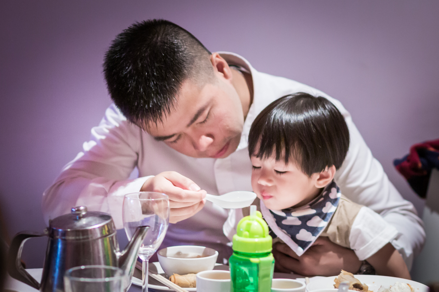 Father feeding soup to little boy at a Chinatown rehearsal dinner