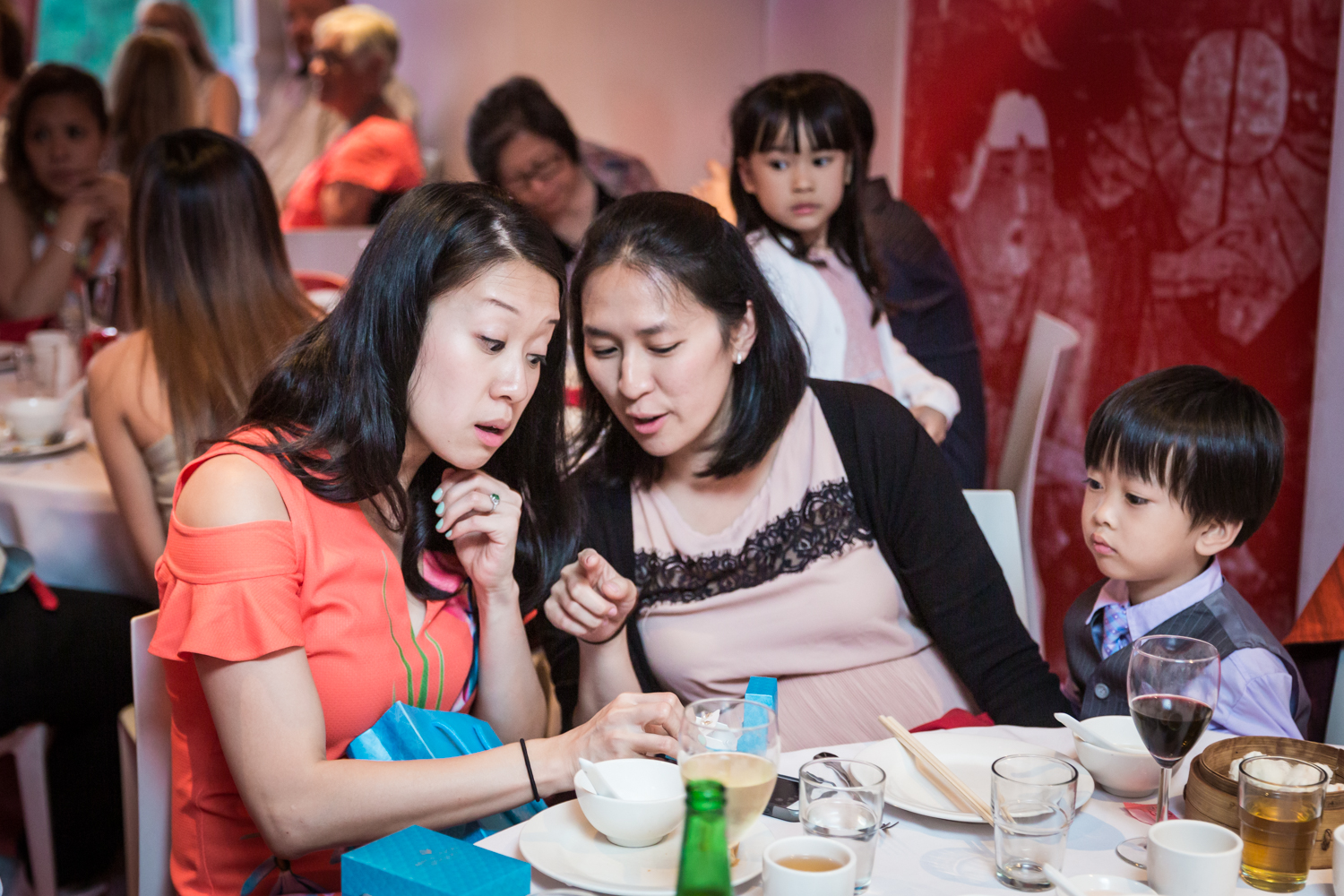 Bride and woman looking at cell phone at a Chinatown rehearsal dinner
