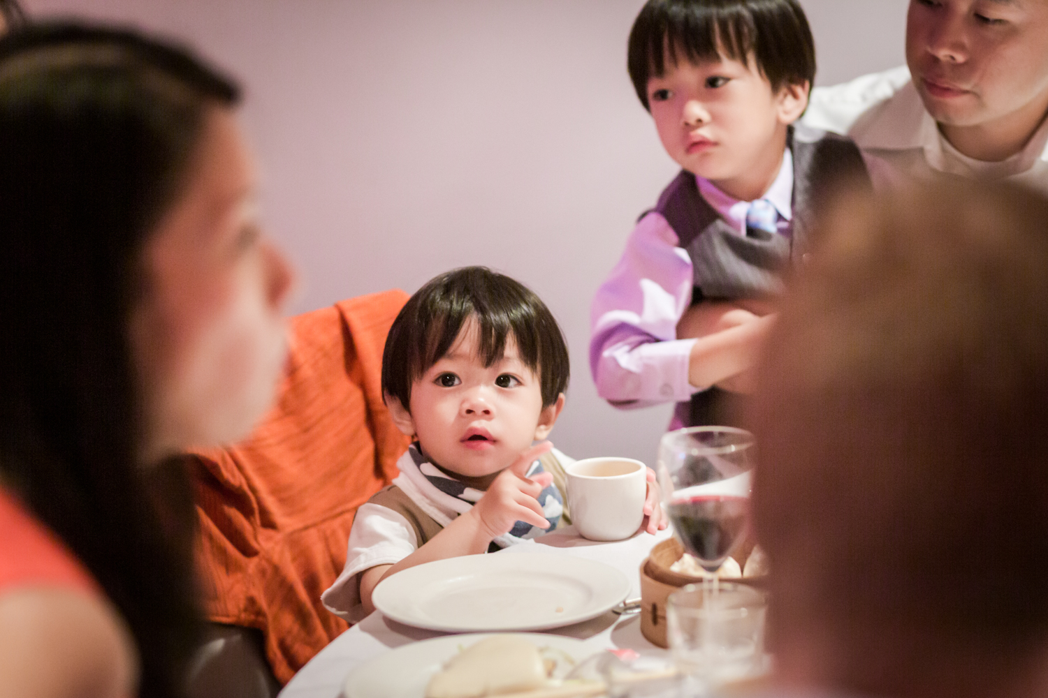 Two little boys watching woman at table
