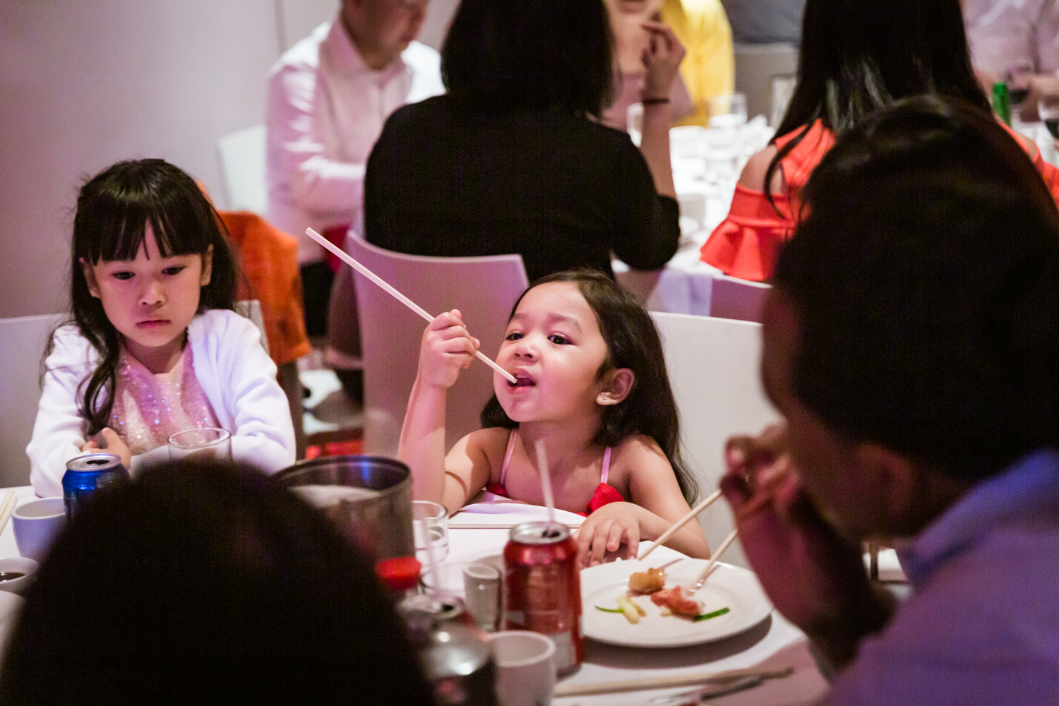 Little girl eating with chopsticks at a Chinatown rehearsal dinner