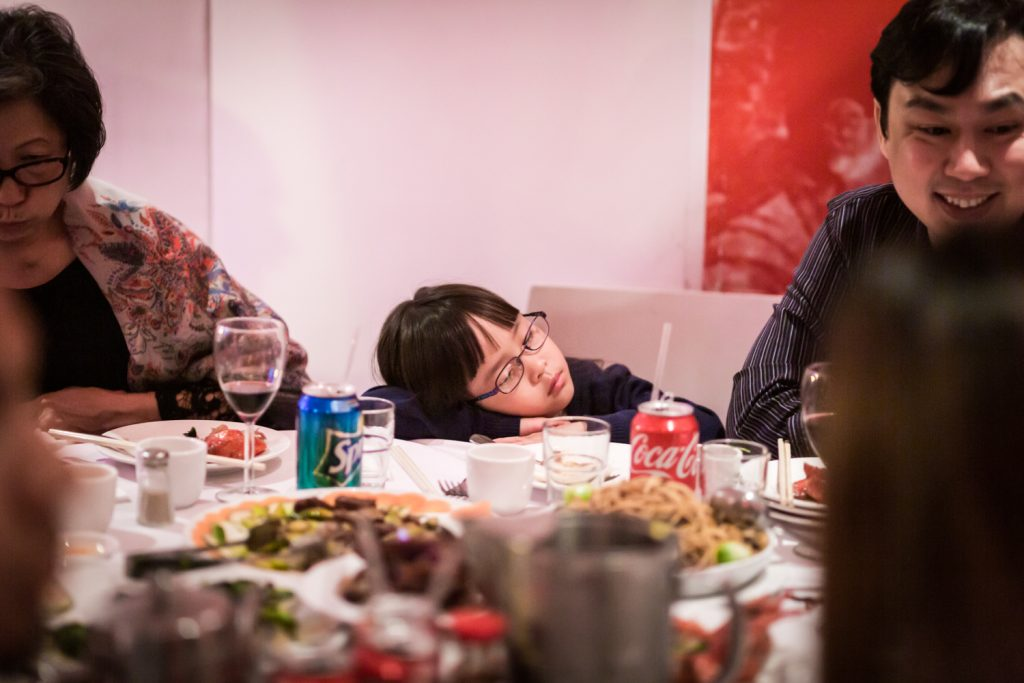 Little girl asleep at table at a Chinatown rehearsal dinner