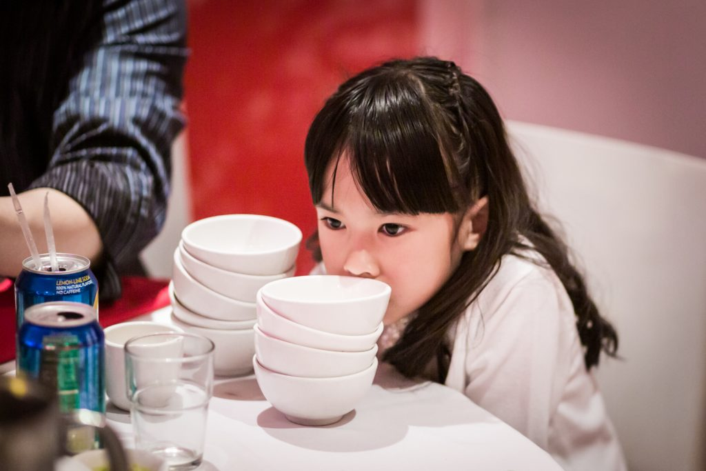 Little girl licking bowls at a Chinatown rehearsal dinner