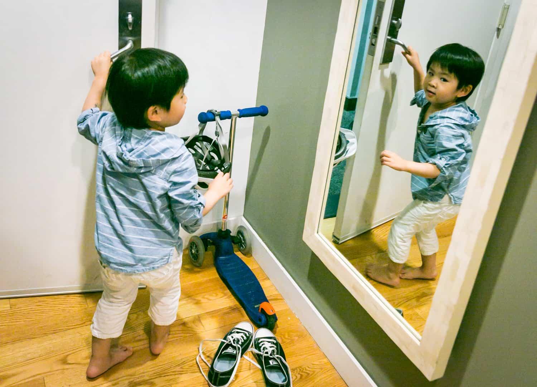 Little boy opening door and reflected in mirror
