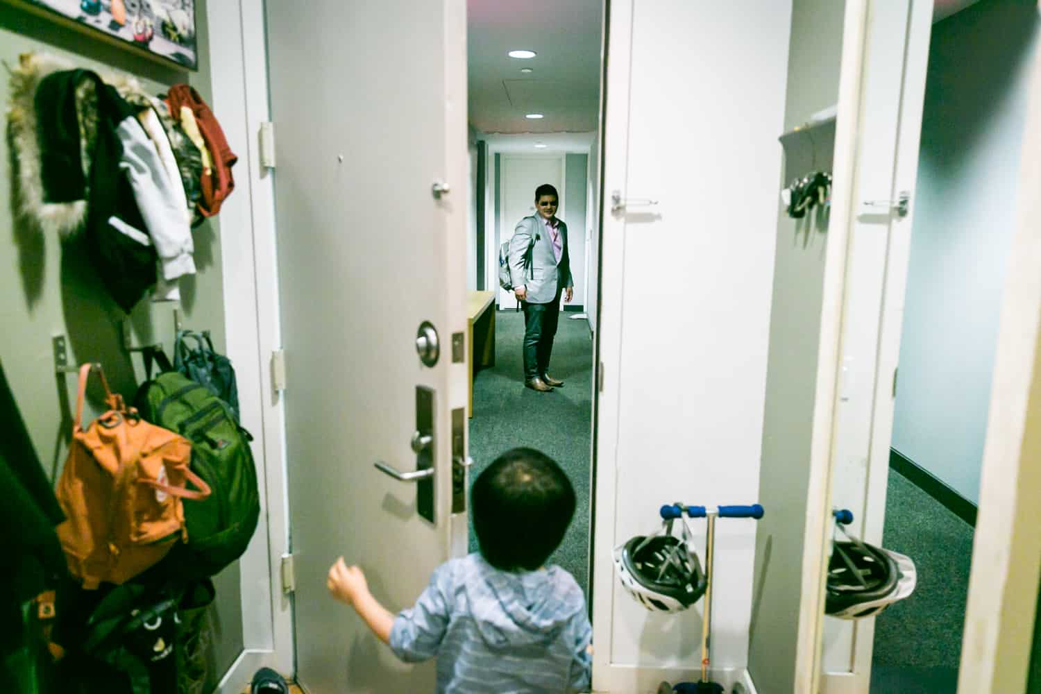 Little boy opening door to see father in hallway