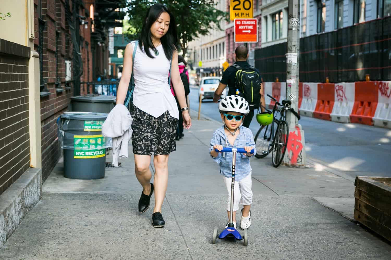 Mother following little boy on scooter wearing helmet