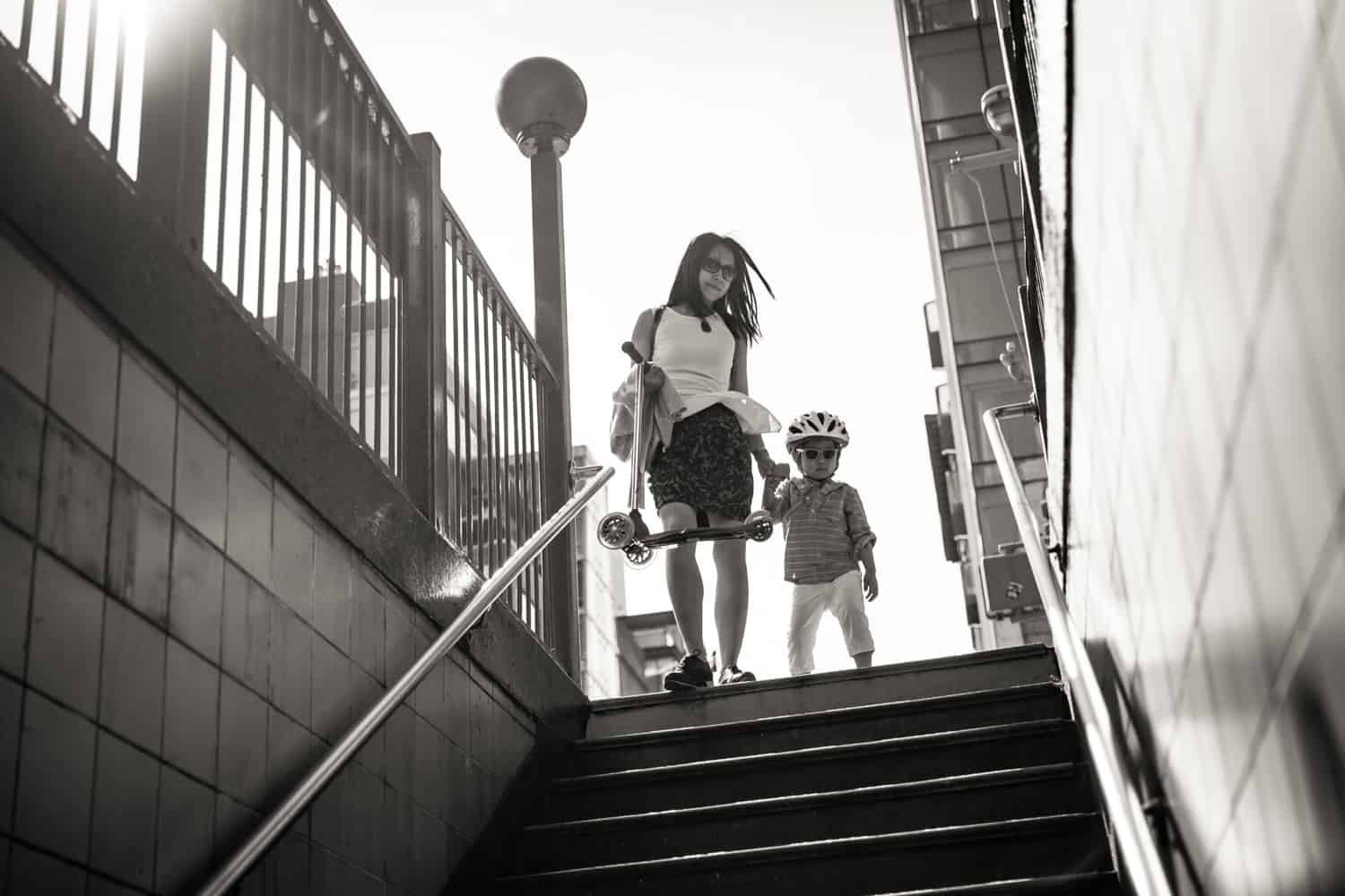 Black and white photo of mother and little boy walking down subway station stairs