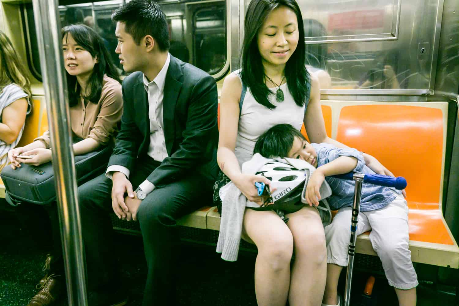 Little boy laying head in lap of mother on subway train