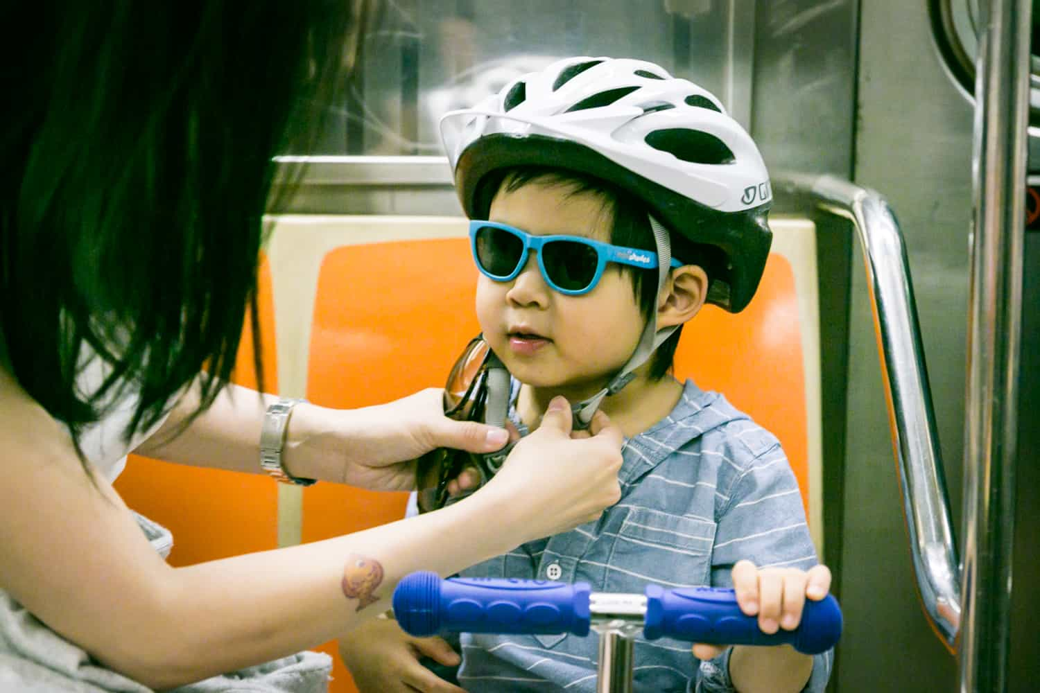 Mother attaching helmet on little boy wearing sunglasses
