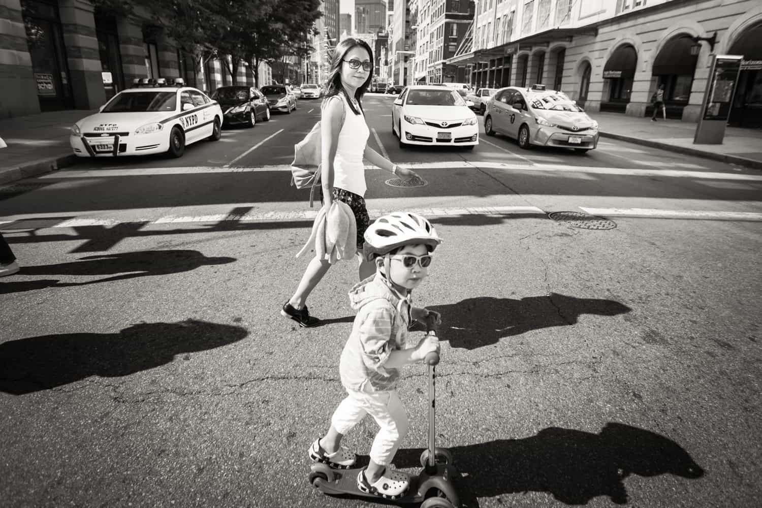 Black and white photo of mother and little boy on scooter walking in crosswalk