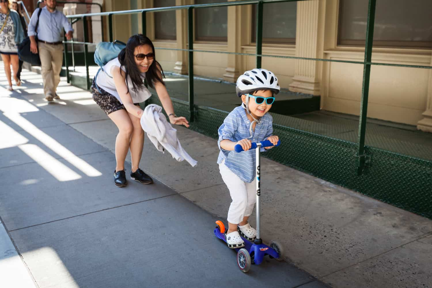 Mother pushing little boy on scooter