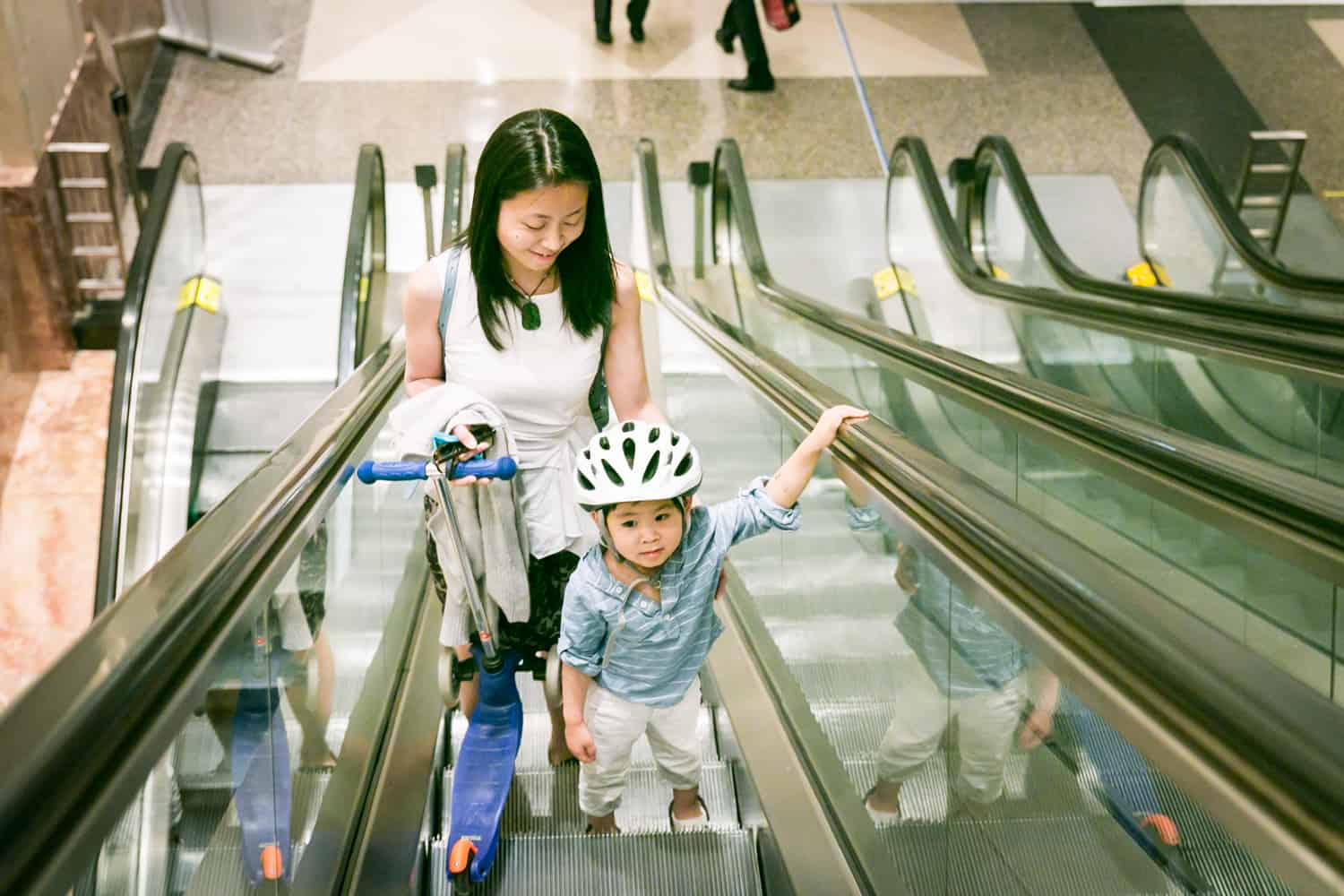 Mother and little boy wearing helmet going up on escalator