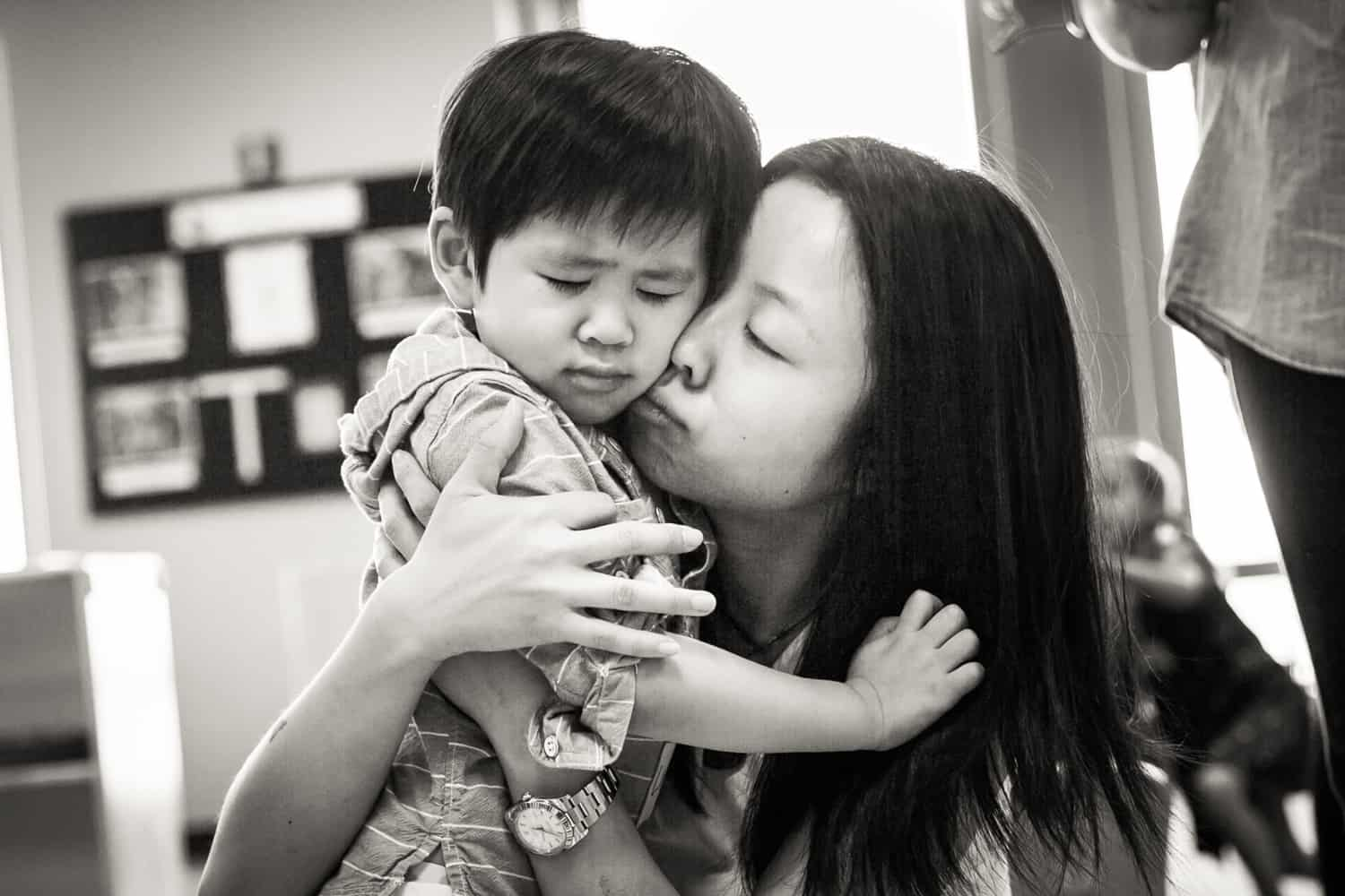 Black and white photo of mother comforting crying little boy