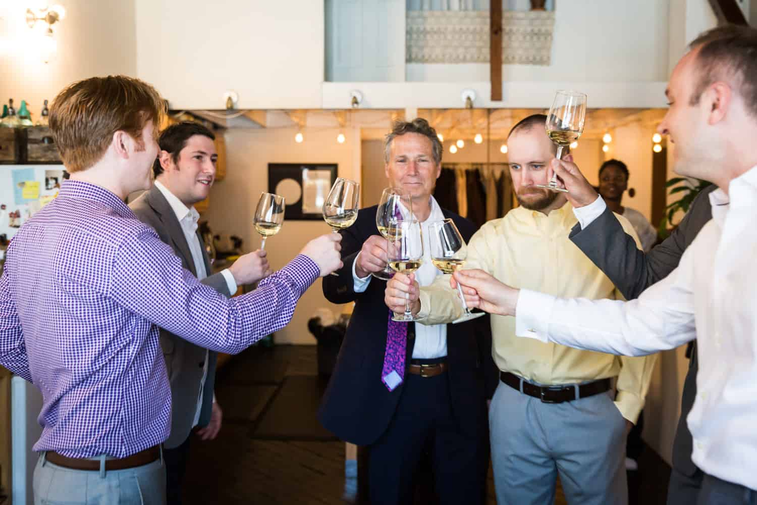 Groom and groomsmen toasting glasses before wedding