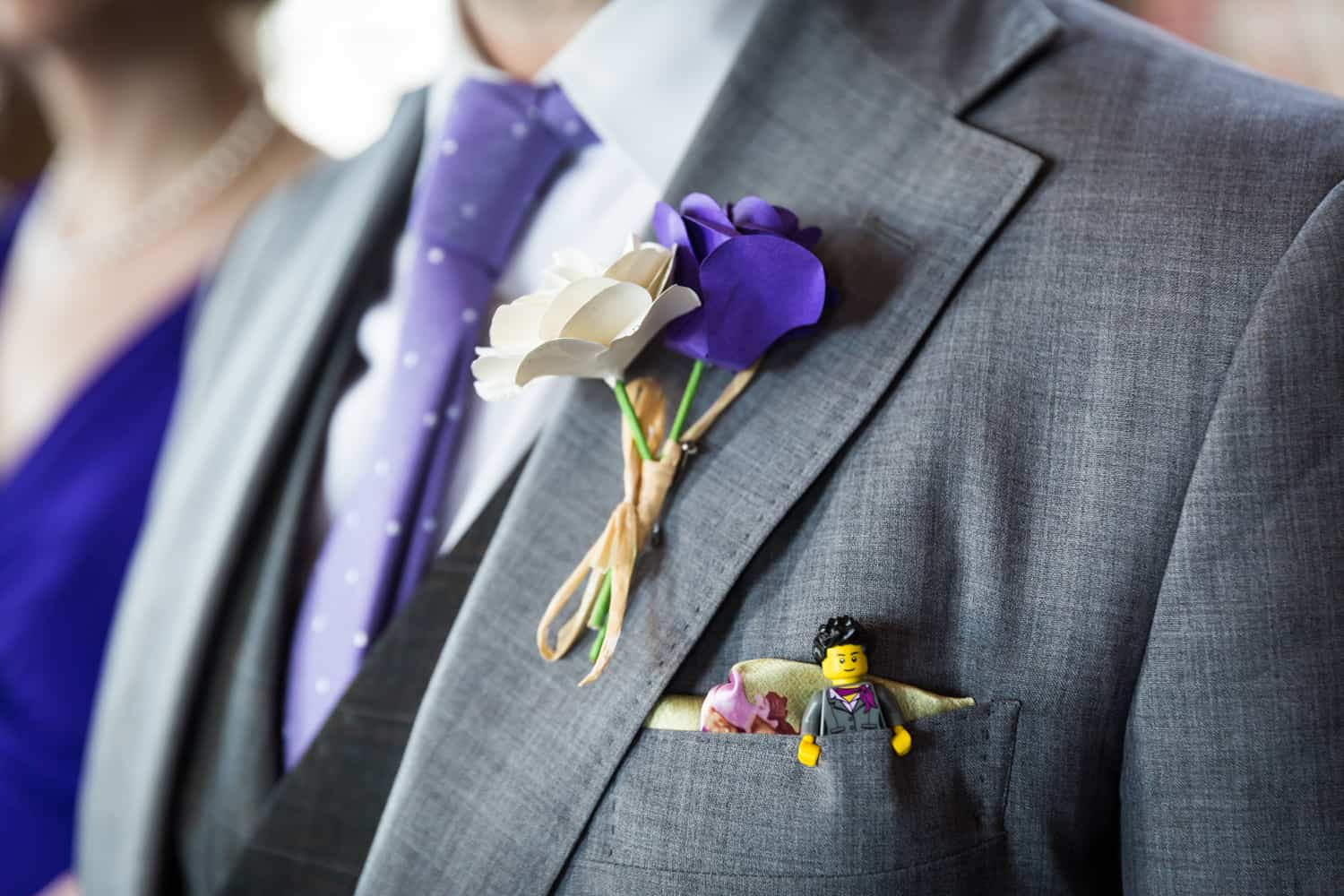 Close up on groom's lapel with purple and white paper flowers and small Lego figure in pocket
