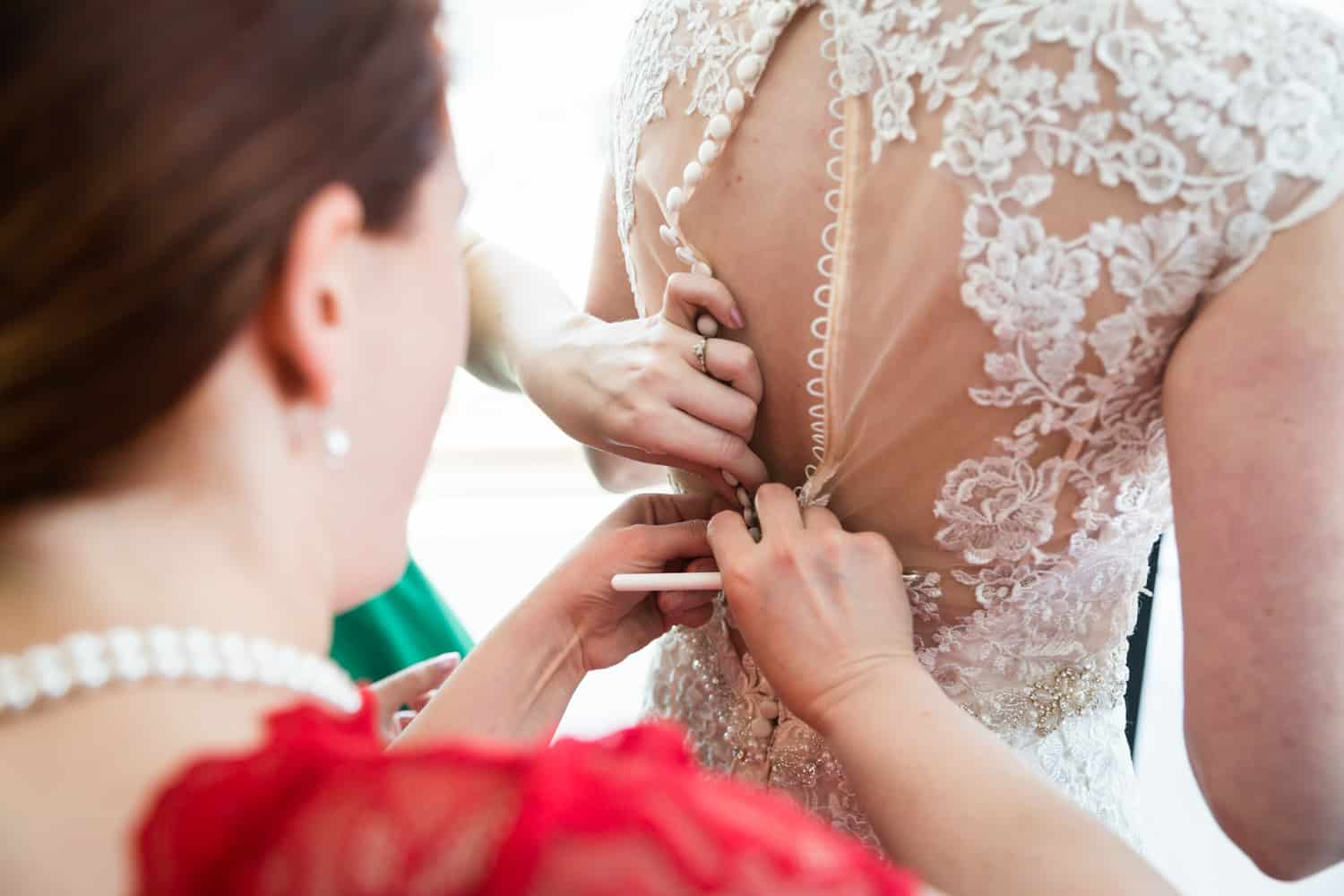 Close up on hands buttoning up bride into wedding dress