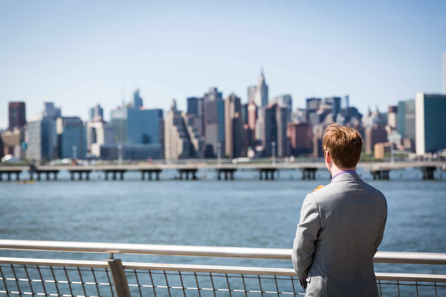 Groom looking out over water to NYC skyline