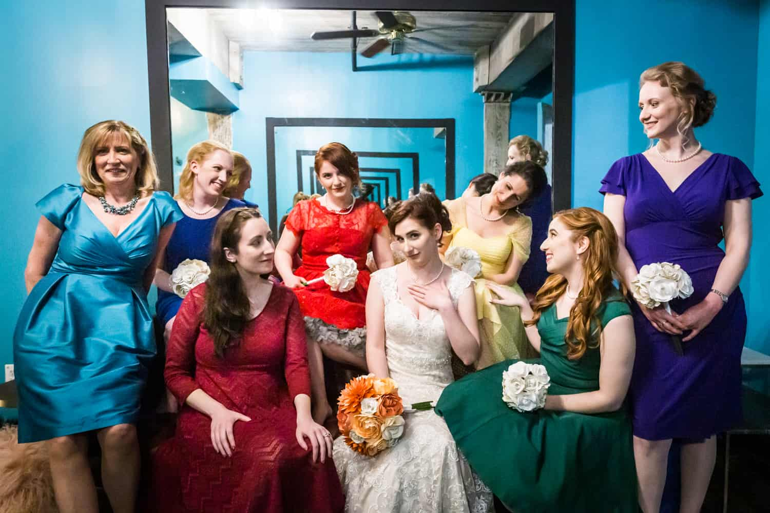 Bridesmaids in blue room wearing different colored dresses at a Greenpoint Loft wedding