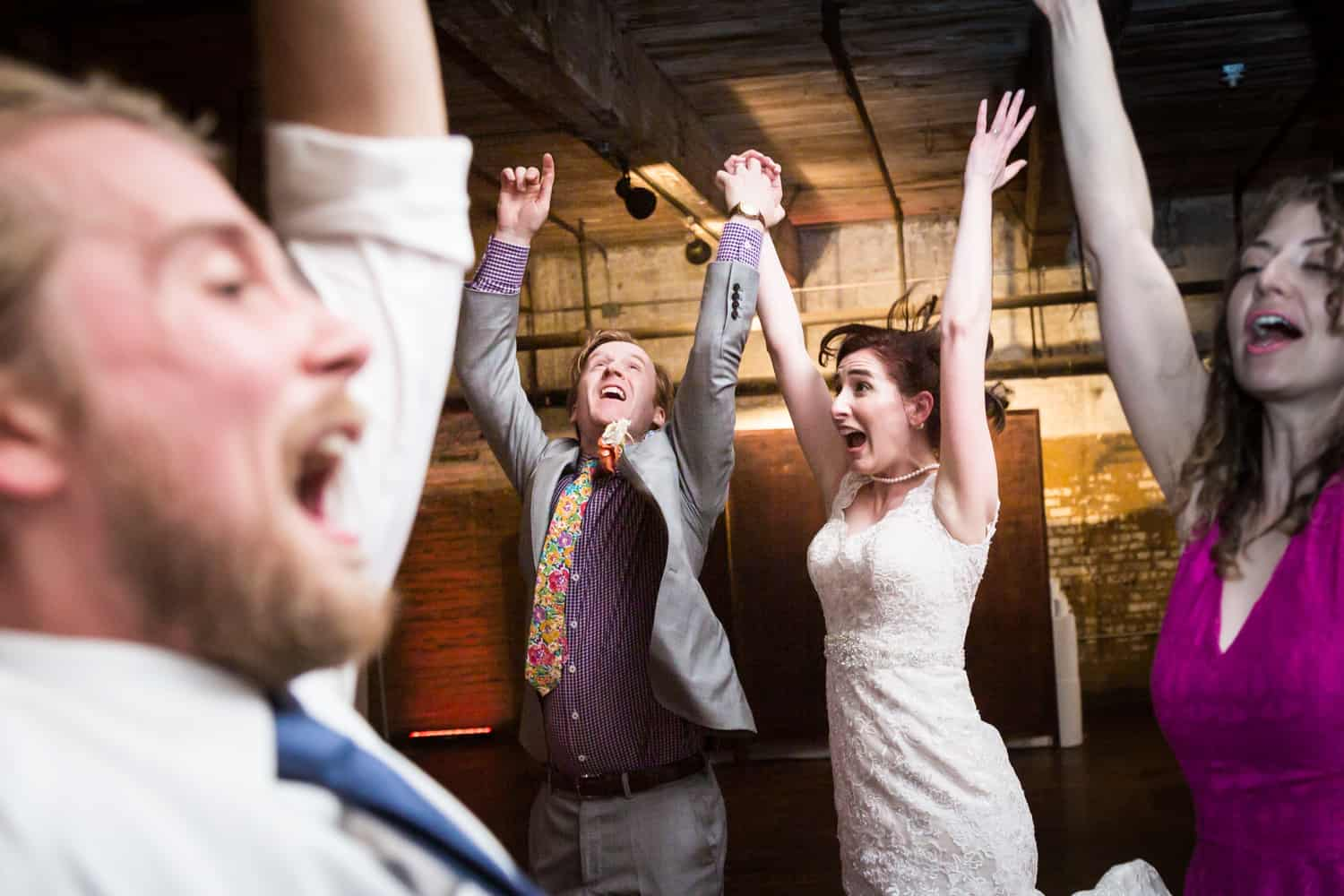 Bride and groom dancing with guests with arms raised at a Greenpoint Loft wedding