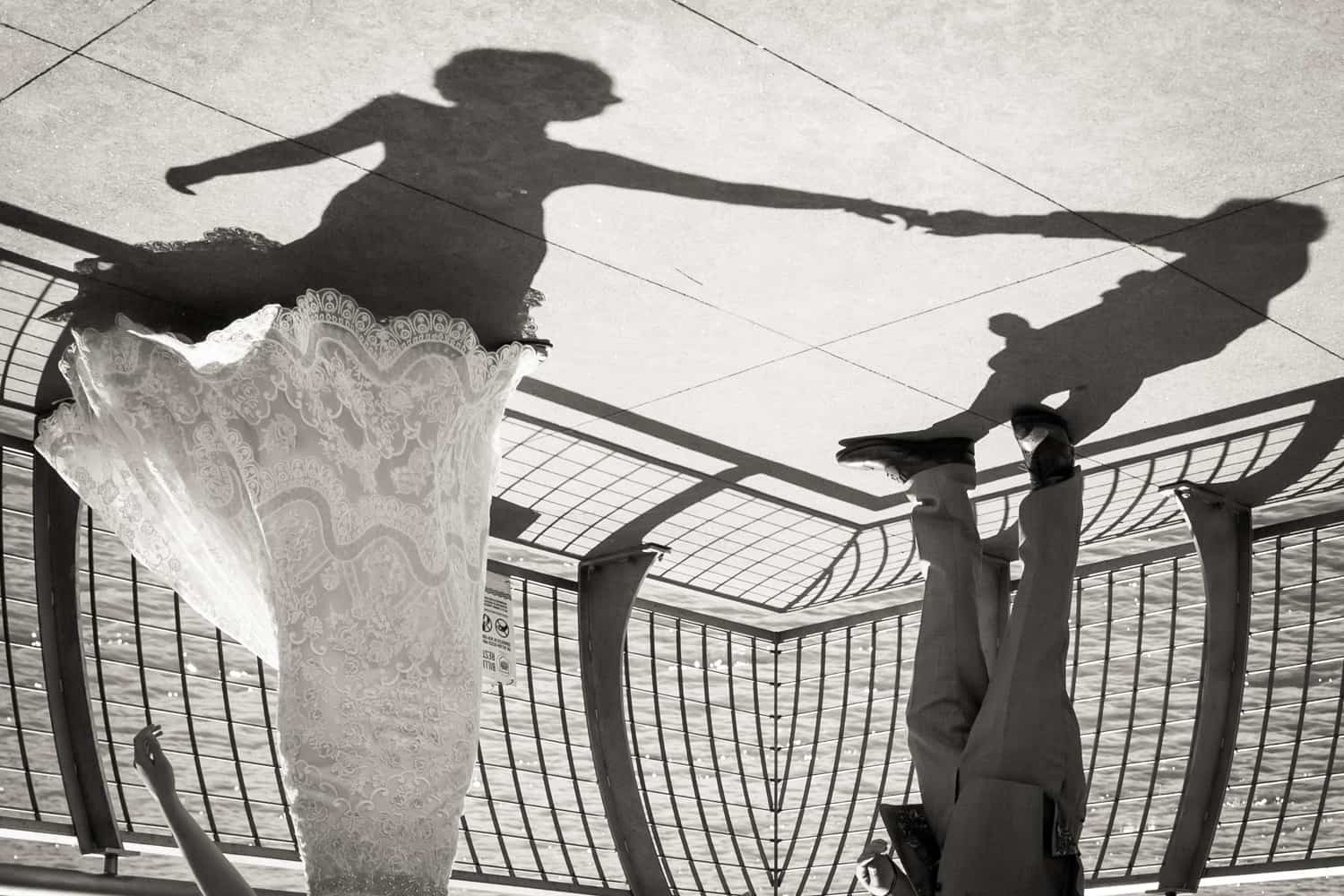 Black and white photo of shadow of bride and groom dancing