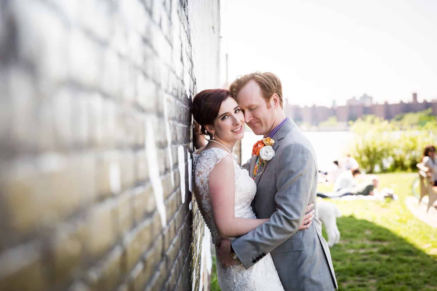 Bride and groom leaning against brick wall at a Greenpoint Loft wedding
