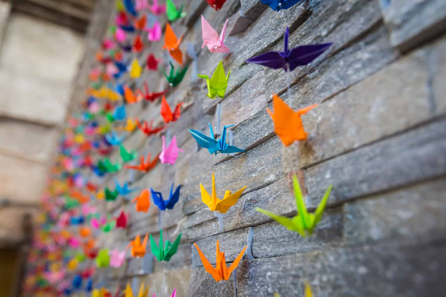 Stone wall with multicolored origami cranes hanging over the wall