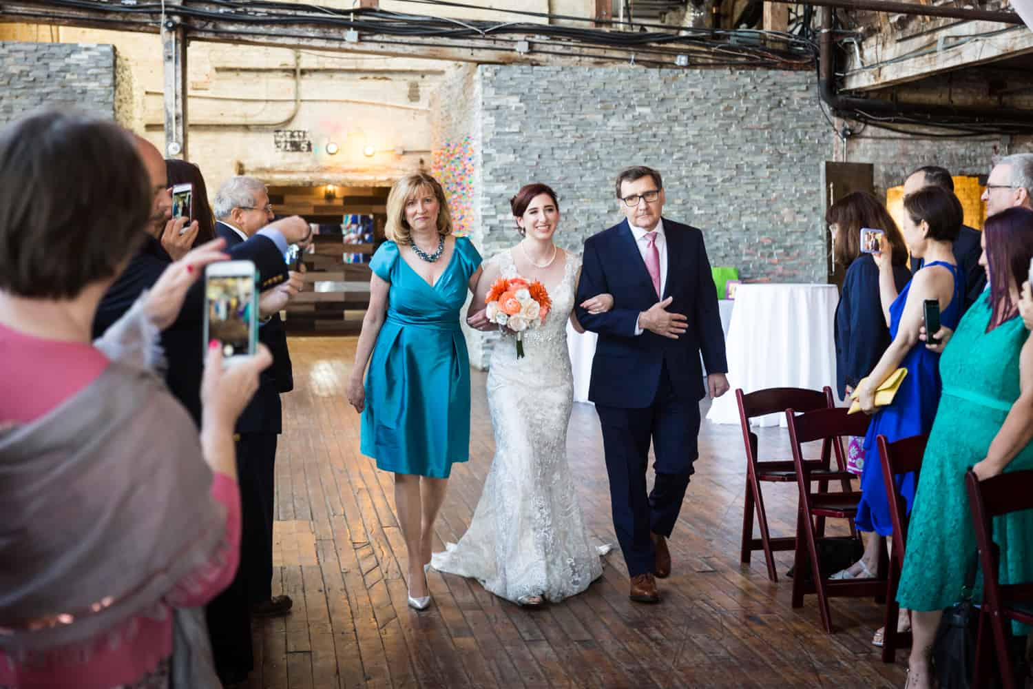 Bride walking up aisle with both parents at a Greenpoint Loft wedding