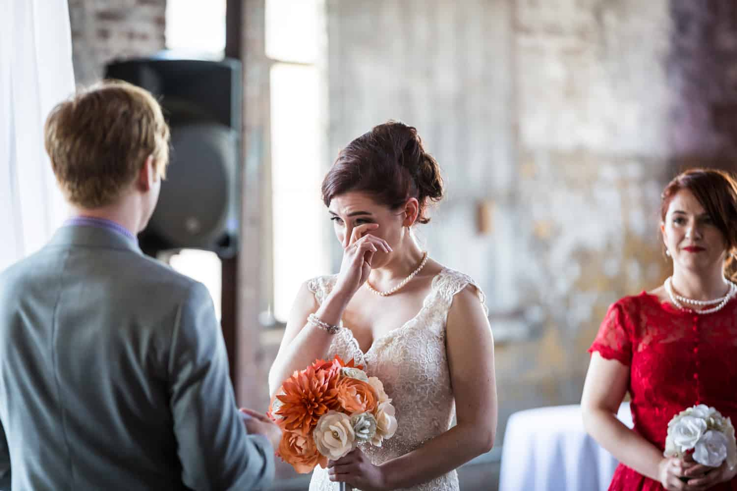 Bride wiping away tear during ceremony at a Greenpoint Loft wedding