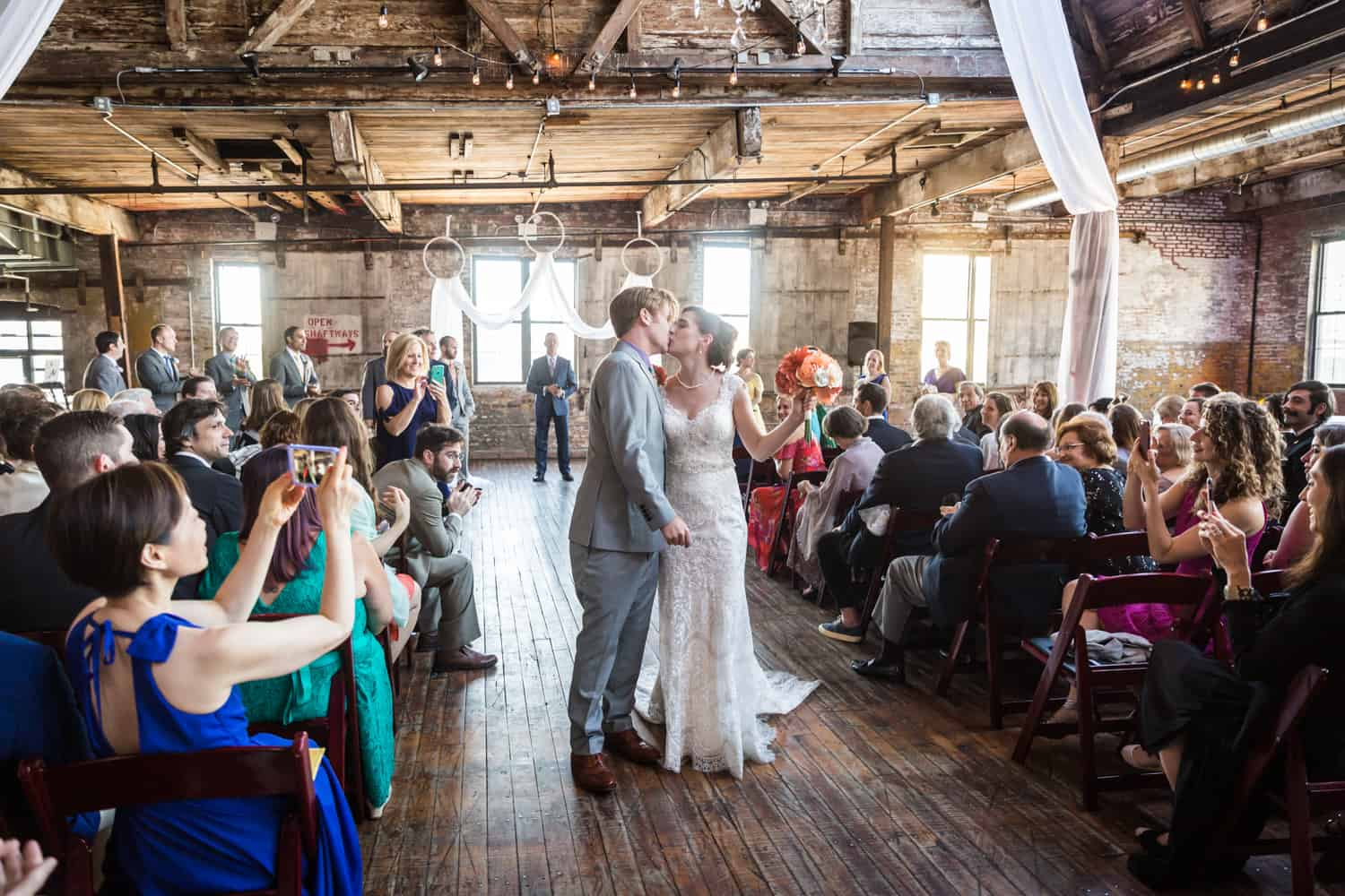 Bride and groom kissing in front of ceremony guests at a Greenpoint Loft wedding