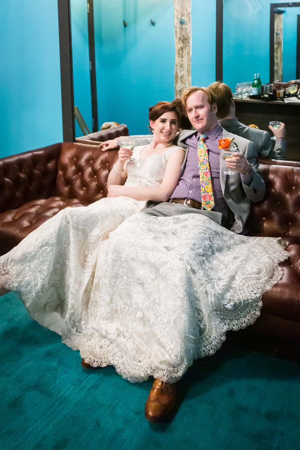 Bride and groom holding cocktails and lounging on couch at a Greenpoint Loft wedding