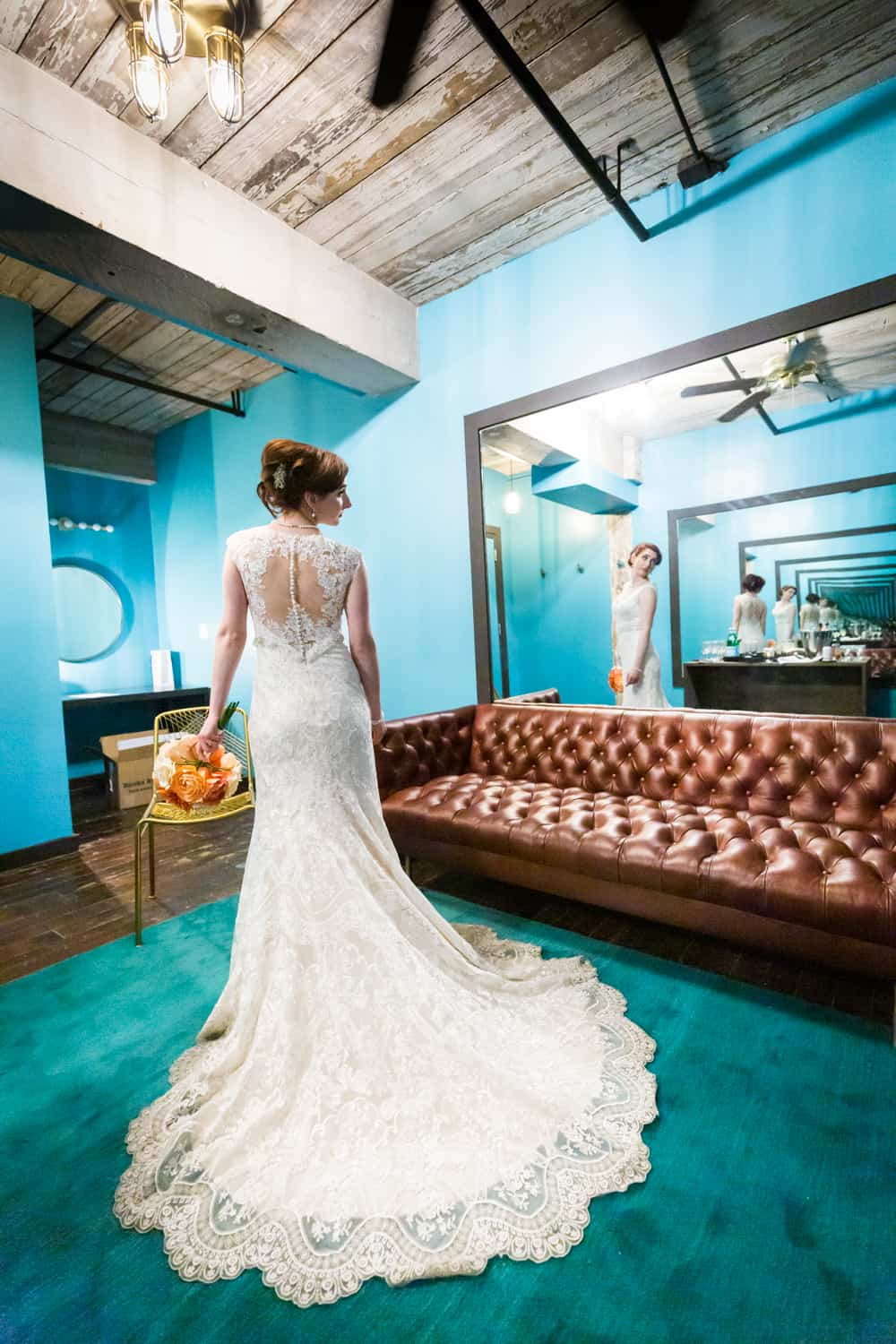 Bride with long train on dress reflected in mirror