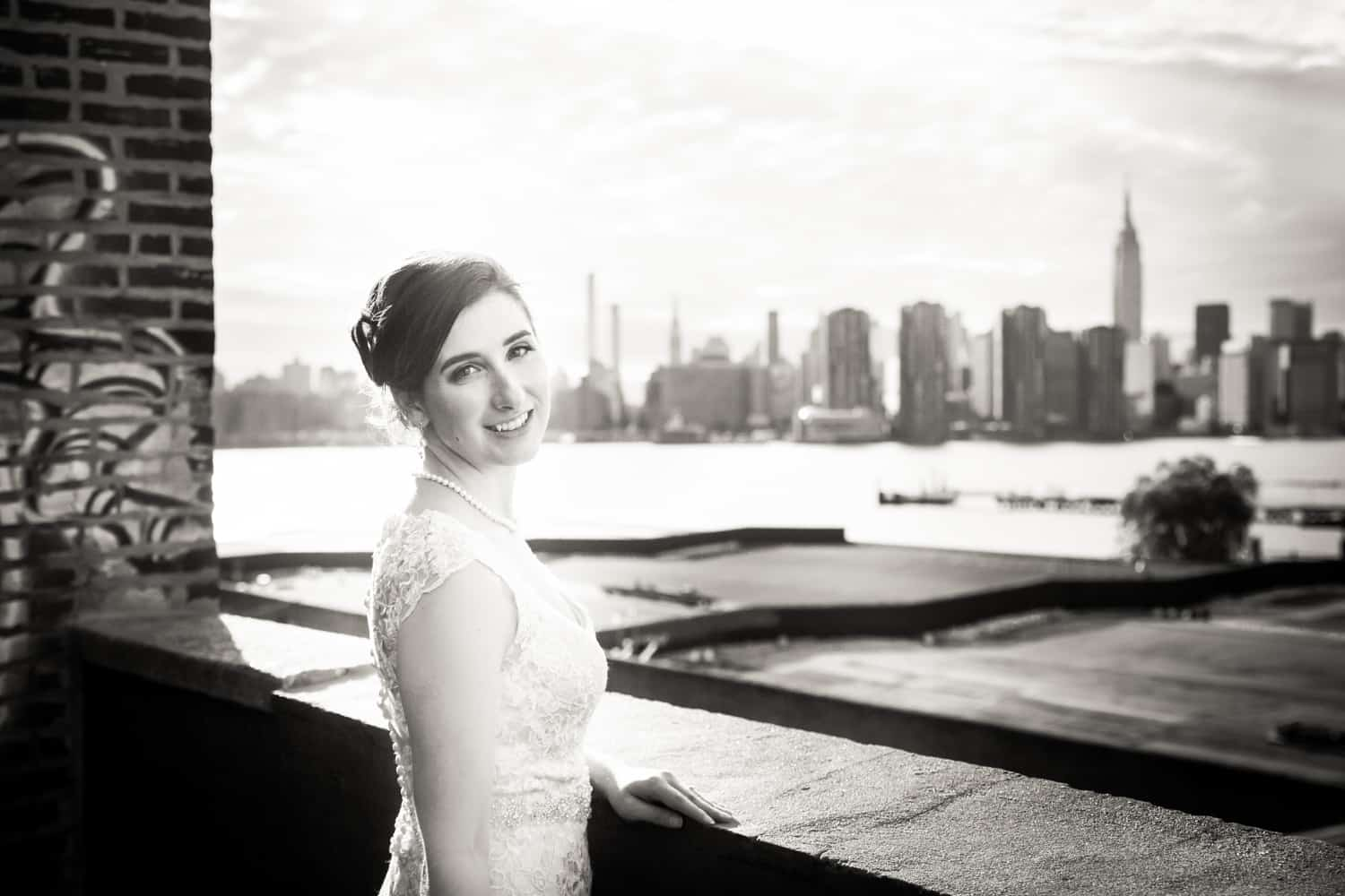 Black and white photo of bride on roof with view of NYC skyline